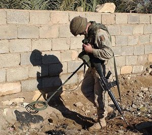 A U.S. Army soldier uses a metal detector to search for weapons and ammunition in Iraq